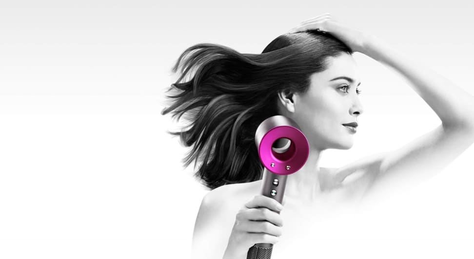 A woman blow dries her hair with the Dyson Supersonic hair dryer