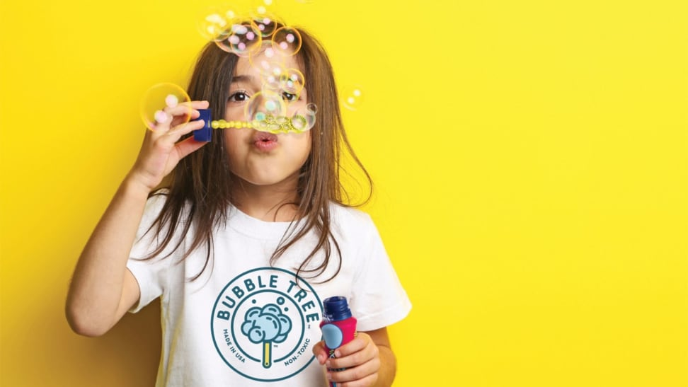 A girl blows bubbles on a yellow background.