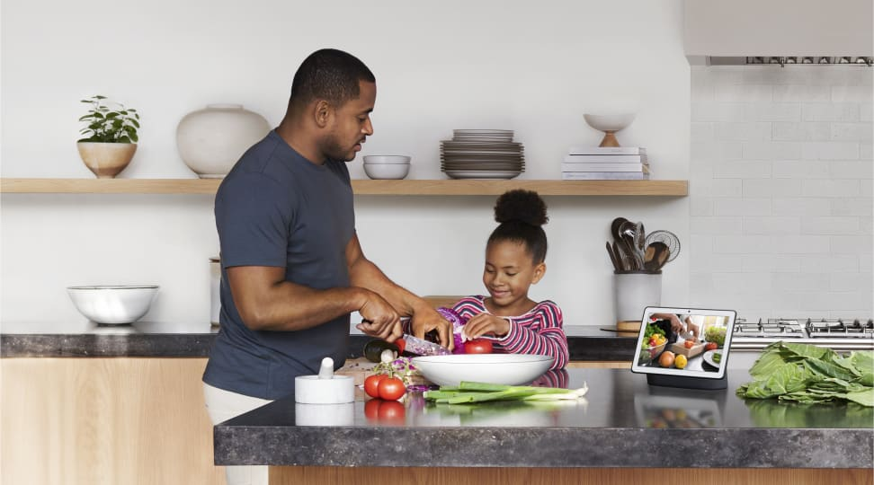 A dad and daughter use the Google Nest Hub Max, one of Google's smart display screens, to cook in the kitchen.