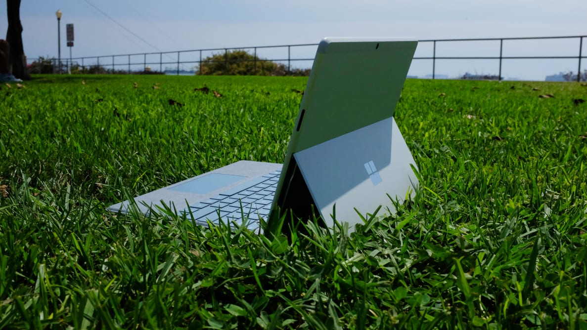 The Surface Pro X, with Type Cover keyboard attached, placed out on a field of grass.