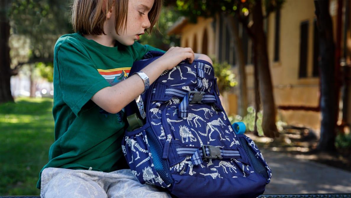 Little boy looking in his school backpack.
