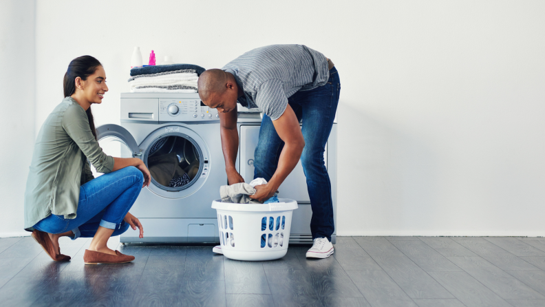 A couple finishes a load of laundry.