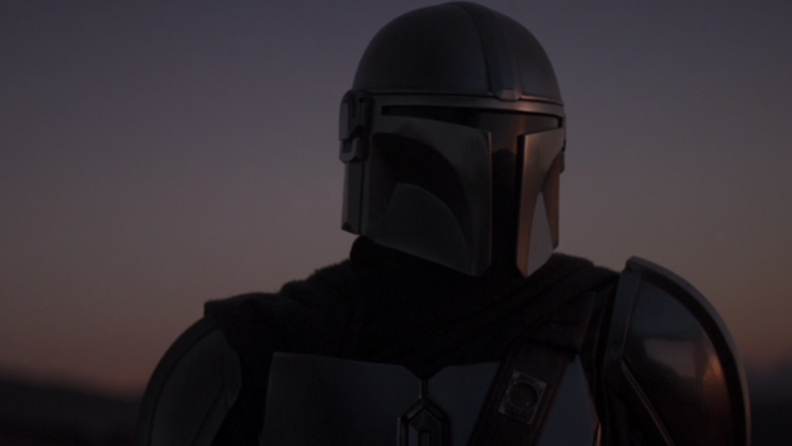 A screenshot from The Mandalorian series featuring the Mandalorian himself against a dark background.