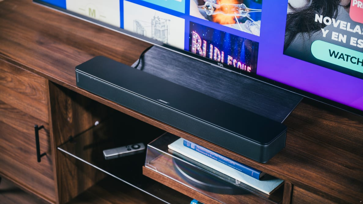 The Bose TV Speaker sits perfectly under a TV, set in all black on a rich wooden cabinet above a record player and other accessories.