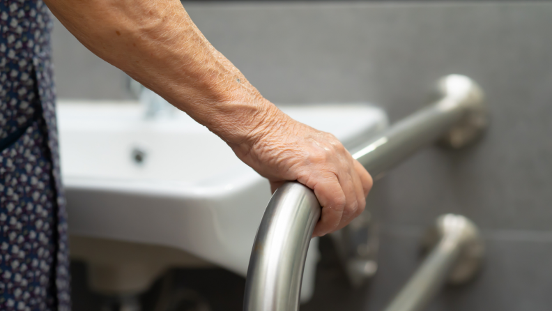 Hand gripping railing in bathroom