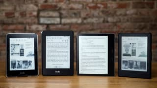 Four Kindles, including the entry-level model, the Paperwhite, and the Oasis, lined up against an exposed brick wall.