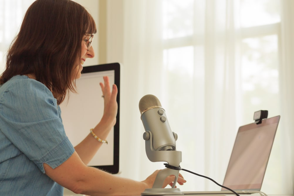 A woman waves hello at her laptop with a large USB microphone in the foreground.