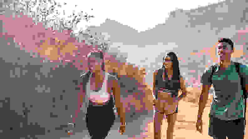 Three friends hiking up a hill.