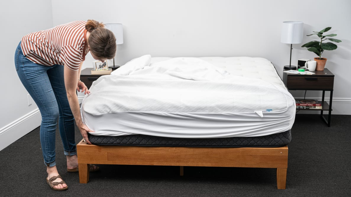 Person putting mattress protector on bed.