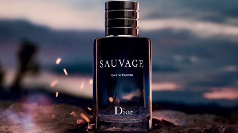 Blue-colored cologne bottle on a blurred twilight background.