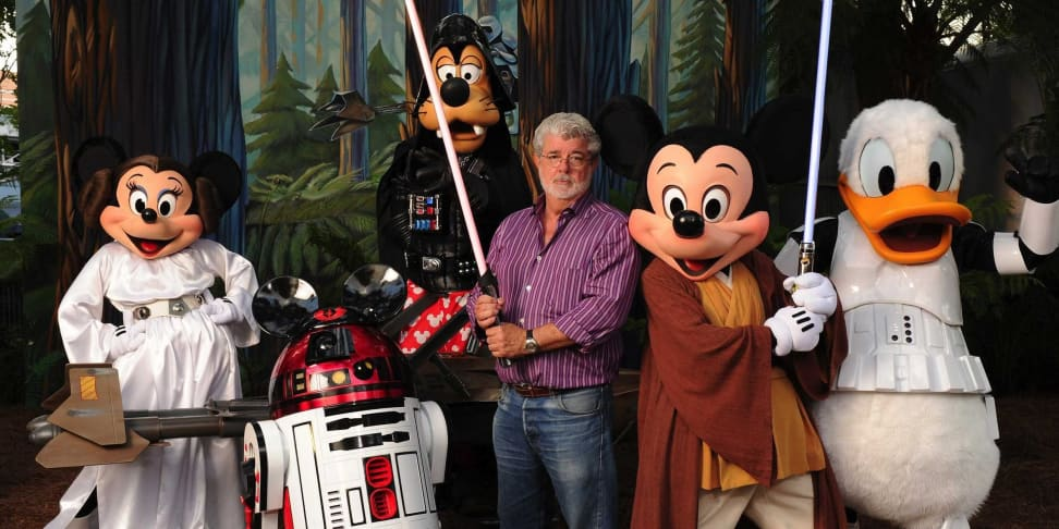 George Lucas posing  with disney characters