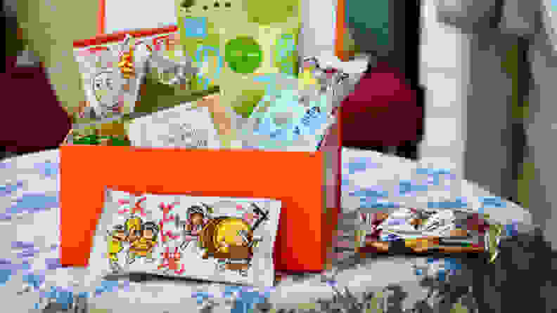 A box of Bokksu Japanese snack subscription box is opened up. Inside the box, there's an assortment of individually-packaged sweet and savory treats.