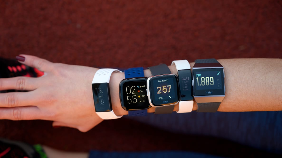 Five different Fitbits worn on a woman's arm