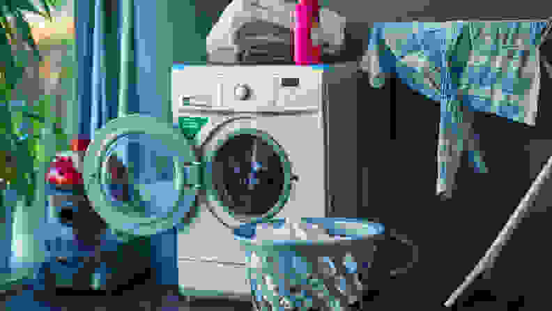 A washer sits in its laundry room, with its door open to dry.