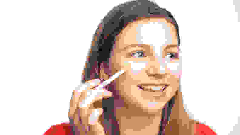 A woman applying concealer to her face.