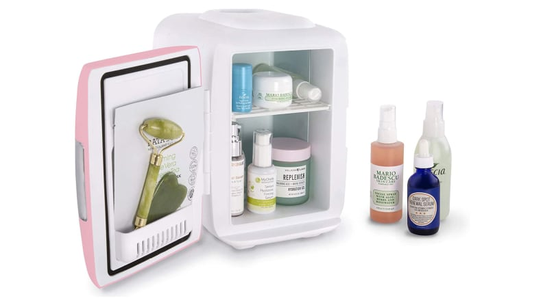 A miniature fridge open to reveal skincare products.