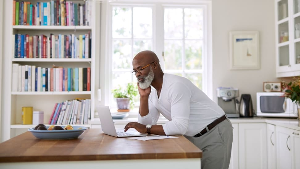 Person standing at butcher block kitchen island while looking at computer screen