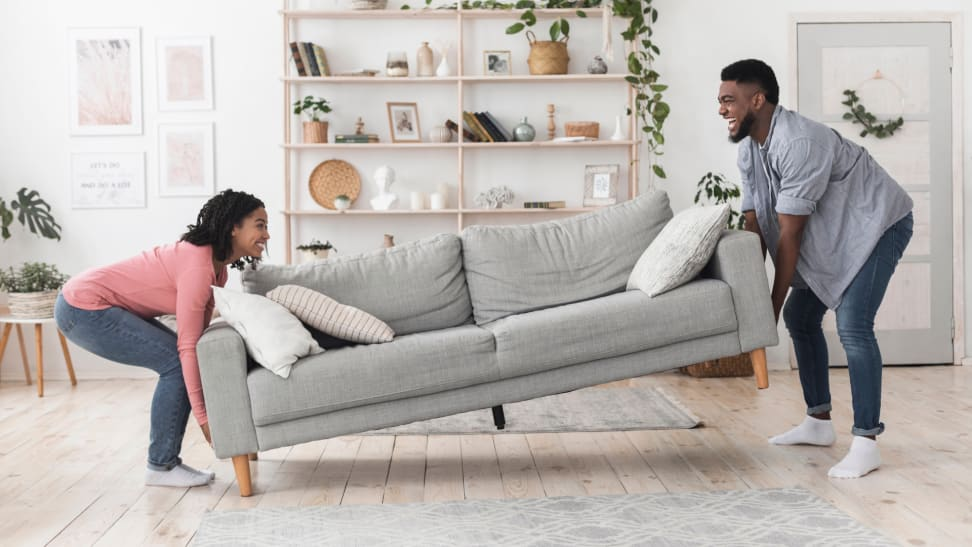 A smiling couple moves a sofa into a living room together.
