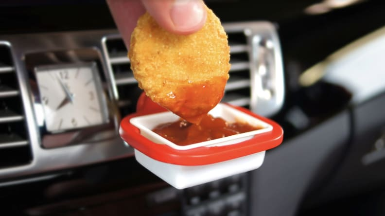 Hand dipping nugget into ketchup dip clip on car vent