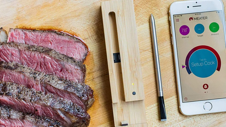 A slab of meat and meat thermometer sit on a butcher block.