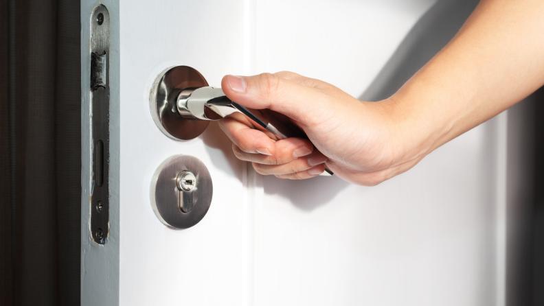 A hand grasps a door lever.