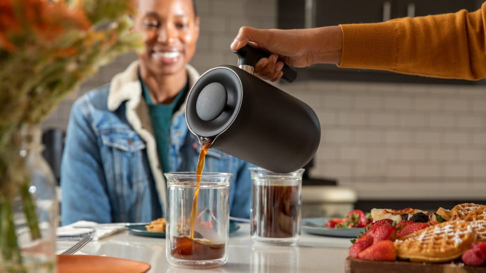 A person is pouring coffee from a Fellow Clara French press coffee maker into a glass mug. A different person is smiling at the mug, watching the coffee pour.