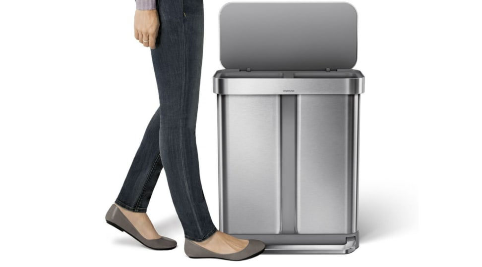 A woman's foot steps on the pedal bar to open the Simplehuman dual compartment trash can.