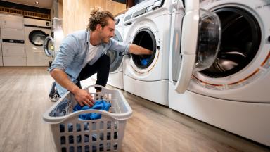 A customer at a self-service laundromat loads a washing machine.