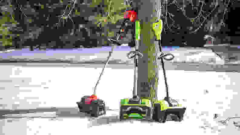 Three electric snow shovels lean up against a tree.