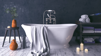 A rustic and dark bathroom with a white standalone tub.