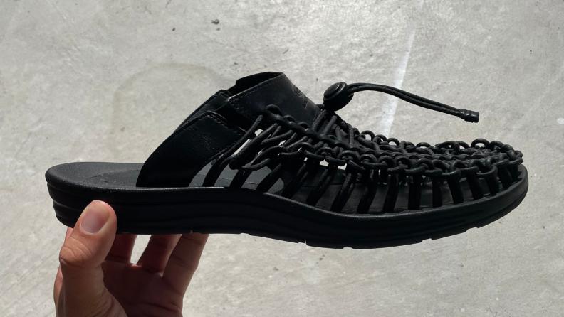 hand holding Keen Uneek Premium Leather Slide