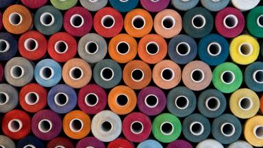 Stacks of multicolored bobbins of fabric.