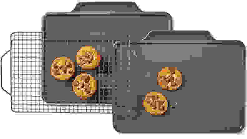 Five cookies sitting on two baking sheets and a baking rack