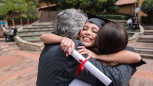 Girl smiling wearing cap and gown hugs parents while holding a diploma in hand.