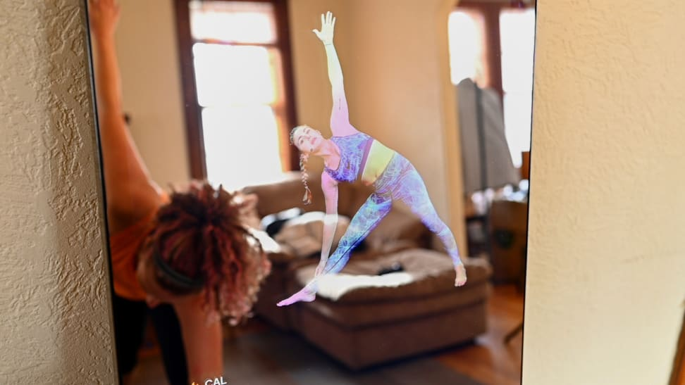 Woman doing yoga in front of lululemon Mirror.