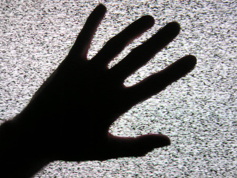 A hand touches a static-filled television screen.
