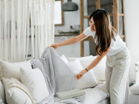 Woman rearranging knit blanket on her couch in her living room