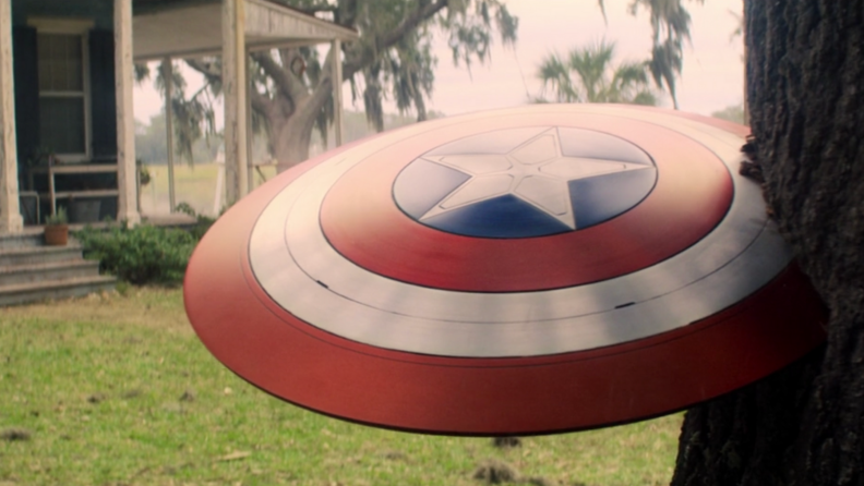 A screenshot from The Falcon and the Winter Soldier featuring Captain America's shield jutting out of a tree trunk.
