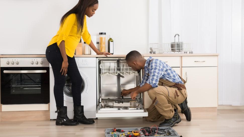 Couple installing dishwasher
