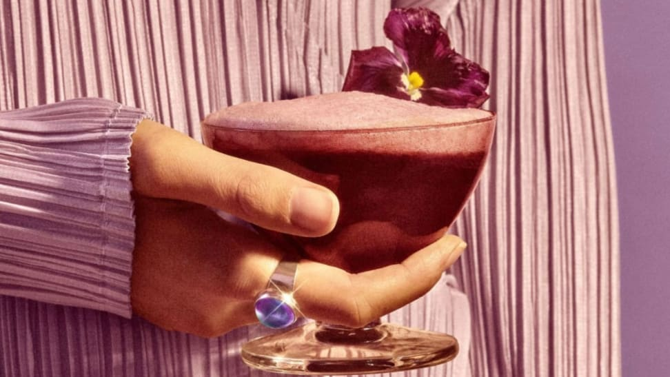 A hand holds a violet-hued cocktail garnished with a tropical flower.