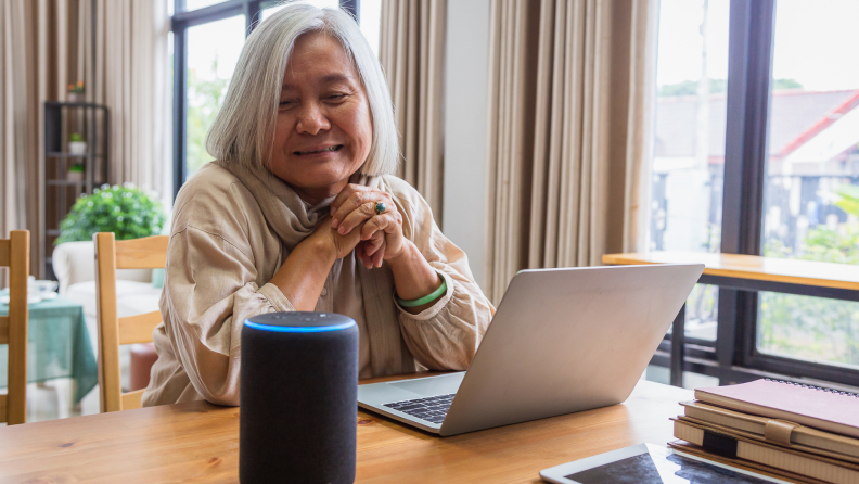 Senior woman sitting at table in front of laptop, next to an Alexa smart device at home.