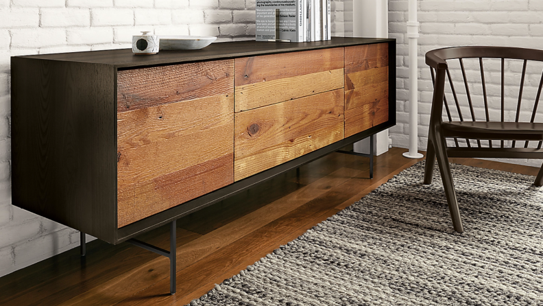 Reclaimed wooden TV console with black hardware on a wood floor next to a rug and chair