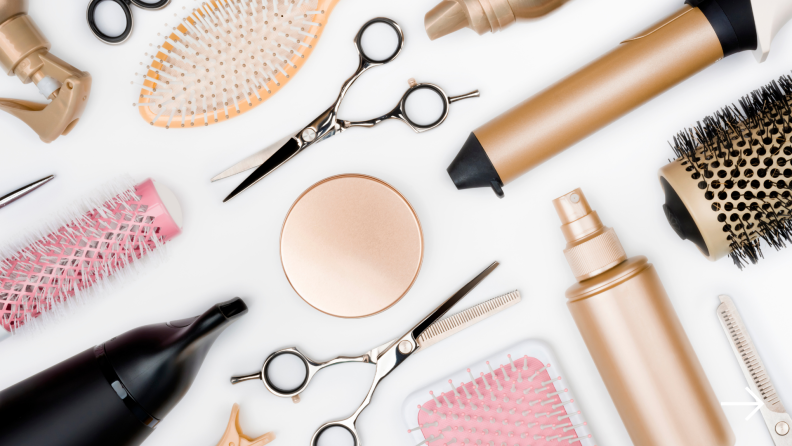 A flat lay image of several hair tools including shears, brushes, and a curling iron.