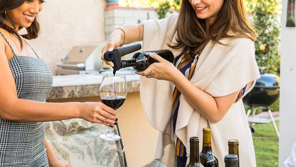 A woman pours a glass of wine using the Coravin Pivot wine preservation system.