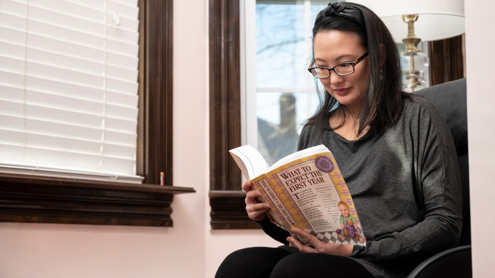 A pregnant woman reads a book about what to expect in the first year of motherhood.