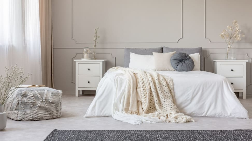 a mostly white bedroom with various fabric blankets