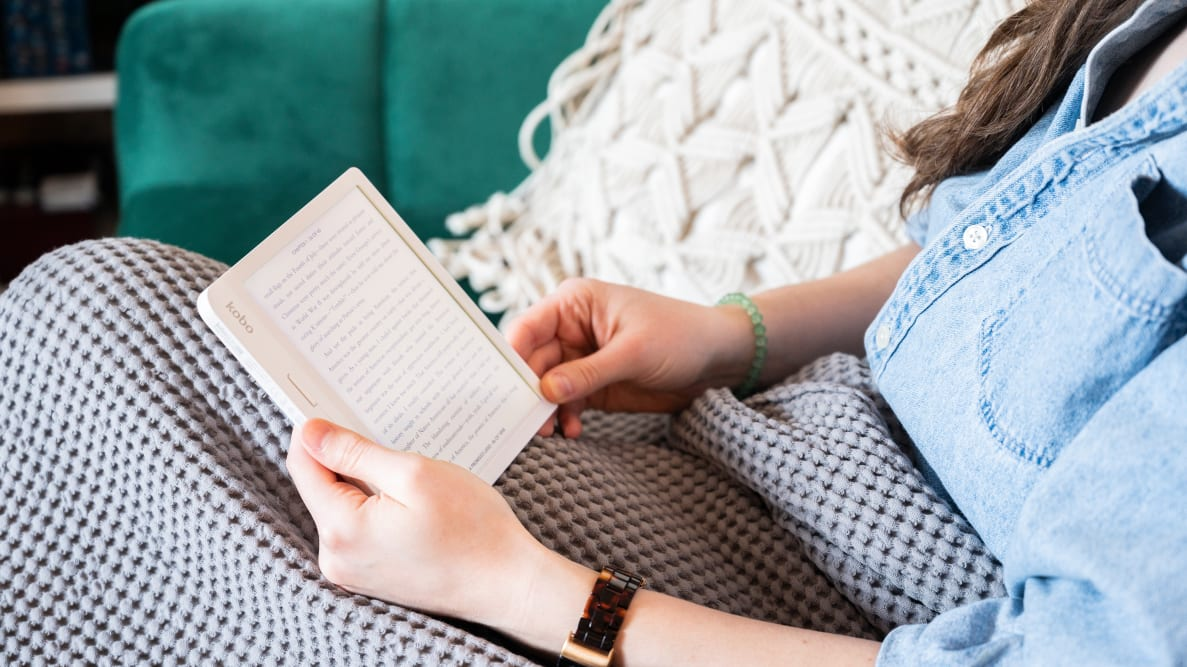 A woman sitting on the couch using an e-reader to read a book.