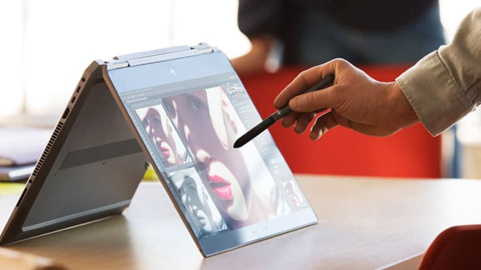 Man drawing on convertible laptop with stylus.