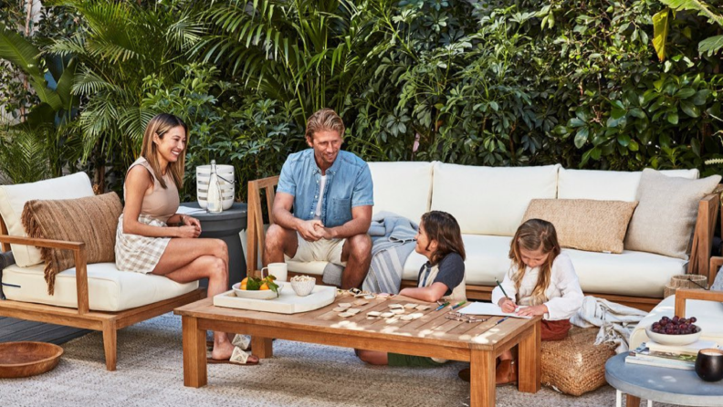 A couple sits with their children on an outdoor sofa.