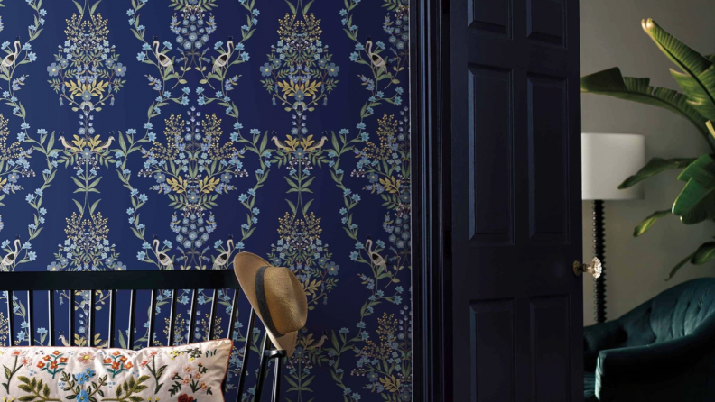 A dark blue wallpaper with a floral design. You can see into a room on the right side of the photo.